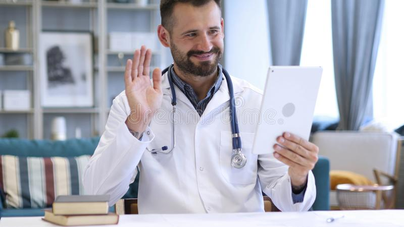 Doutor Sharing Good News no bate-papo video na tabuleta imagens de stock