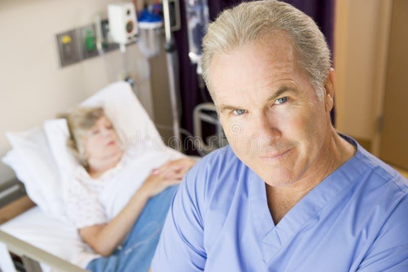 Doutor Standing Paciente Quarto, olhando sério fotografia de stock