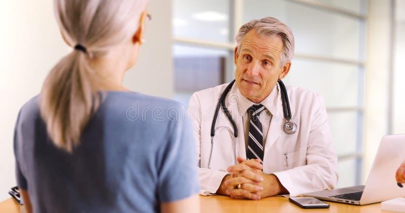 Doutor superior bem sucedido que discute interesses da saúde com a mulher idosa fotos de stock royalty free