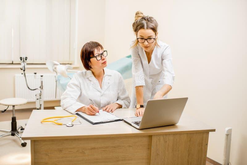Doutor superior com o assistente novo no escritório gynecological imagens de stock