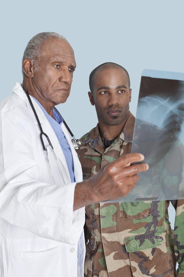Doutor superior com o soldado dos E.U. Marine Corps que olha o relatório do raio X sobre a luz - fundo azul imagens de stock
