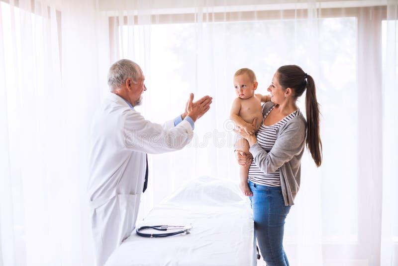 Doutor superior, mãe e um bebê em um escritório fotografia de stock