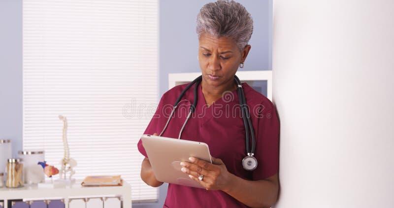 Doutor superior preto sério que trabalha na tabuleta no escritório foto de stock royalty free