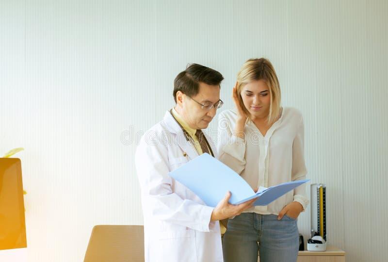 Doutor superior que examina ao paciente da jovem mulher e ao tratamento da continuação no hospital imagens de stock