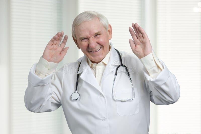 Doutor superior que ri duramente com mãos levantadas acima foto de stock royalty free