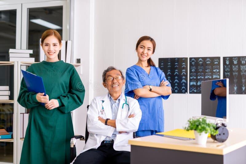 Doutor superior que senta-se no centro da equipe com enfermeira e o retrato fêmea do doutor Surgeon no escritório no hospital imagens de stock royalty free