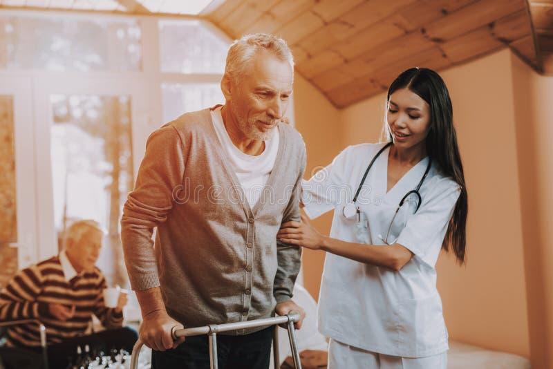 Doutor Supports Man Pensionista em kart ajudas imagens de stock