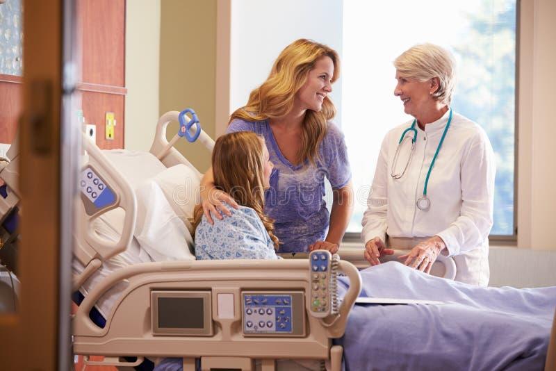 Doutor Talks To Mother com a filha adolescente no hospital imagem de stock