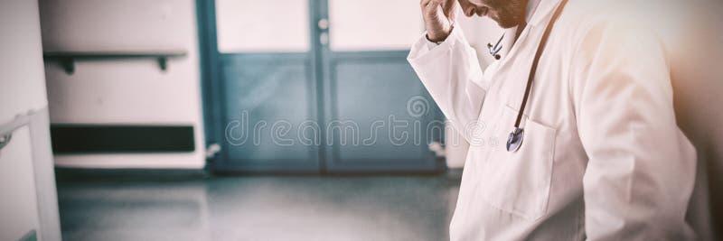 Doutor triste que inclina-se contra a parede imagens de stock