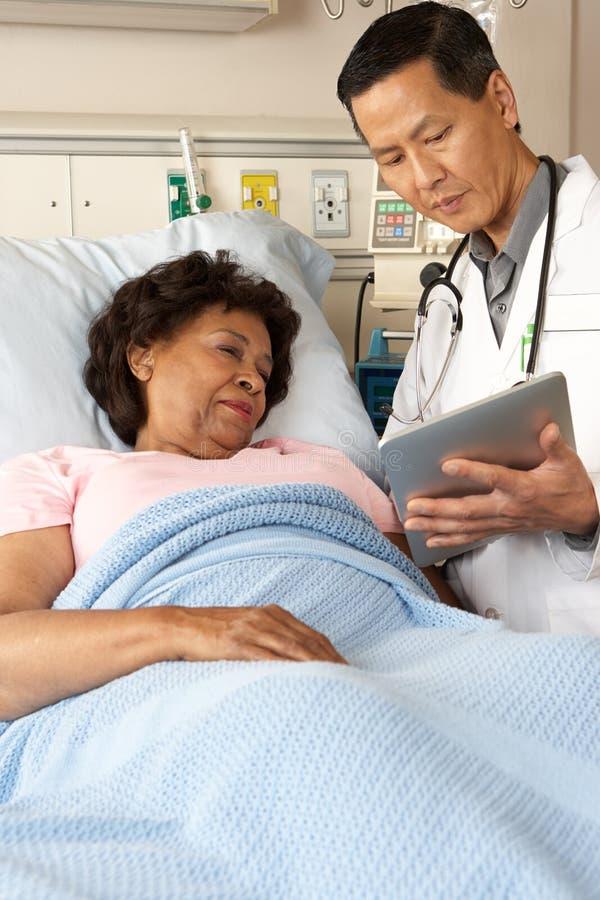 Doutor Utilização Digital Tabuleta Talking com paciente superior fotografia de stock royalty free