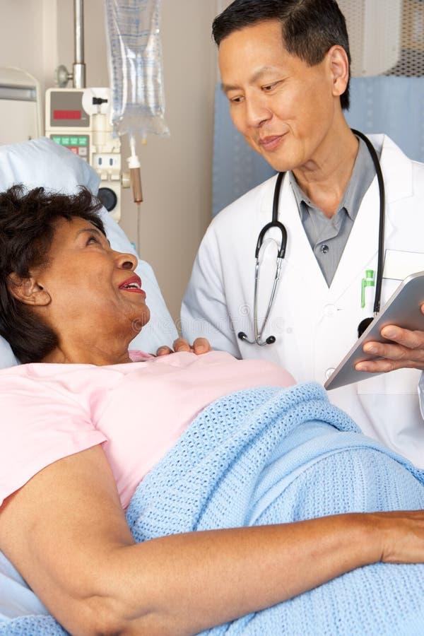 Doutor Utilização Digital Tabuleta Talking com paciente superior imagem de stock royalty free