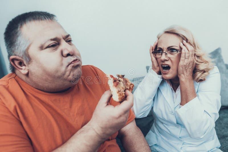 Doutor virado no revestimento perto do homem gordo com pizza fotografia de stock