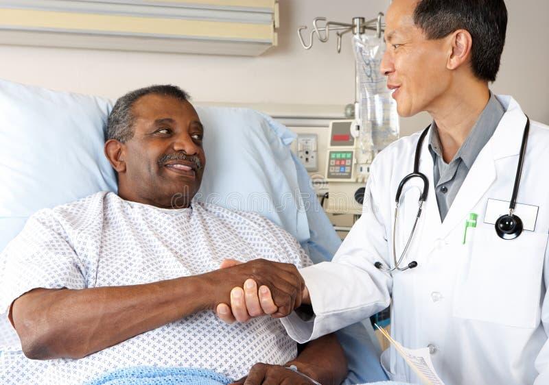 Doutor Visiting Superior Homem Paciente na divisão fotografia de stock royalty free