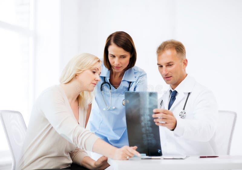 Doutores com o paciente que olha o raio X foto de stock royalty free