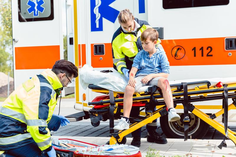 Doutores da emergência que importam-se com o menino da vítima do acidente fotografia de stock royalty free