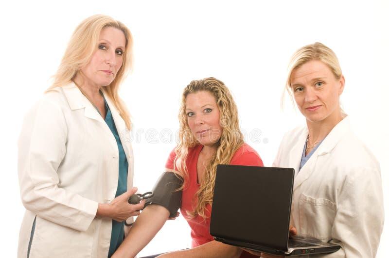 doutores das enfermeiras fêmeas com paciente imagem de stock royalty free