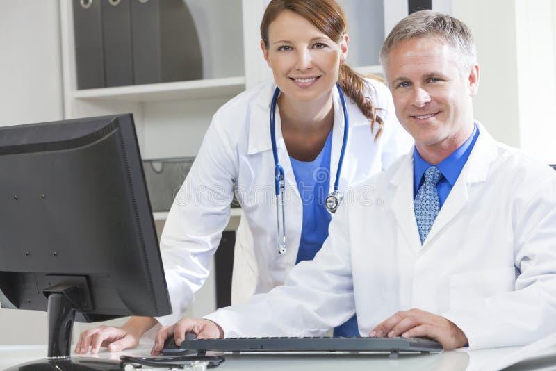 Doutores de hospital fêmeas masculinos que usam o computador