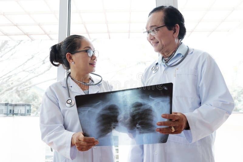 Doutores de sorriso com raio X do paciente recuperado imagens de stock