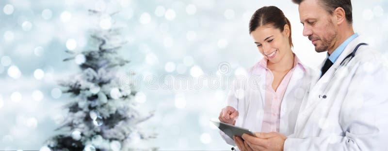 Doutores do Natal com a tabuleta digital em luzes borradas com tre foto de stock royalty free