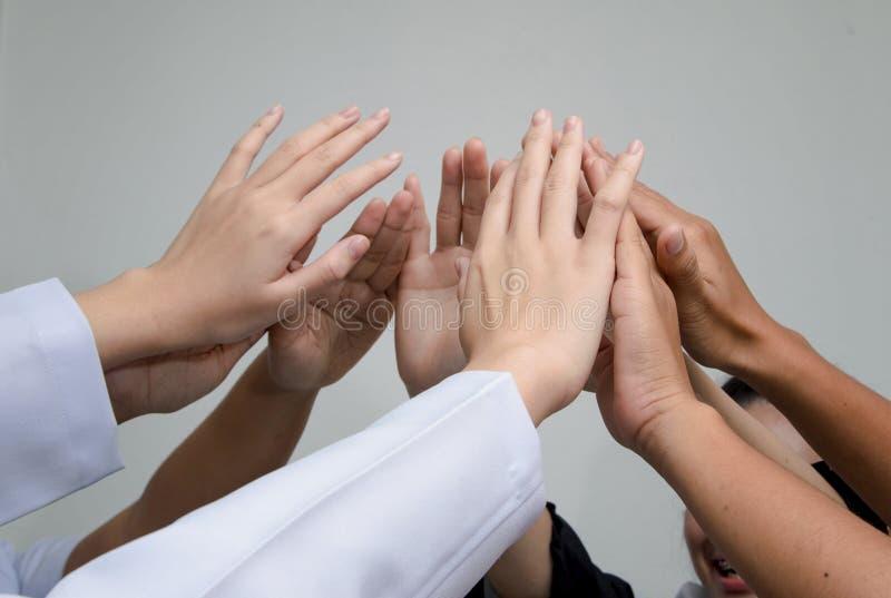 Doutores e enfermeiras em uma equipa médica que empilha as mãos fotografia de stock