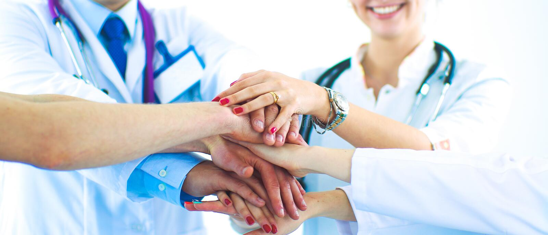 Doutores e enfermeiras em uma equipa médica que empilha as mãos fotografia de stock royalty free