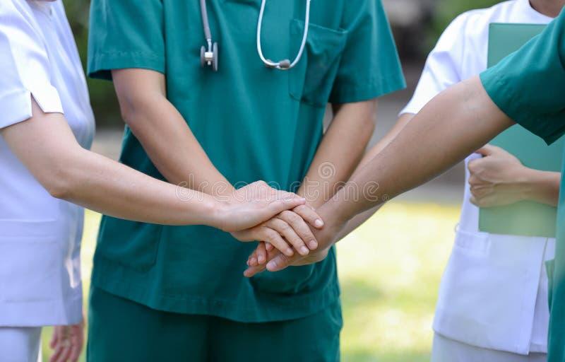 Doutores e enfermeiras em uma equipa médica que empilha as mãos exteriores em t imagens de stock royalty free