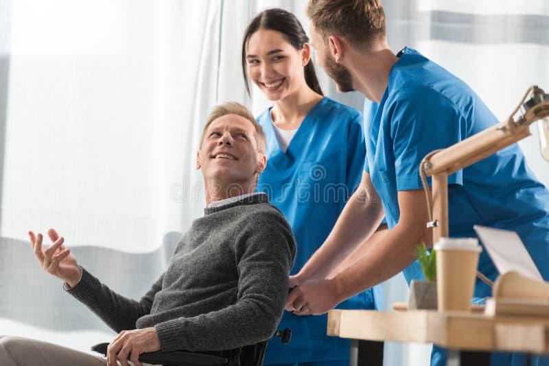 doutores e paciente de sorriso na fala da cadeira de rodas imagem de stock royalty free