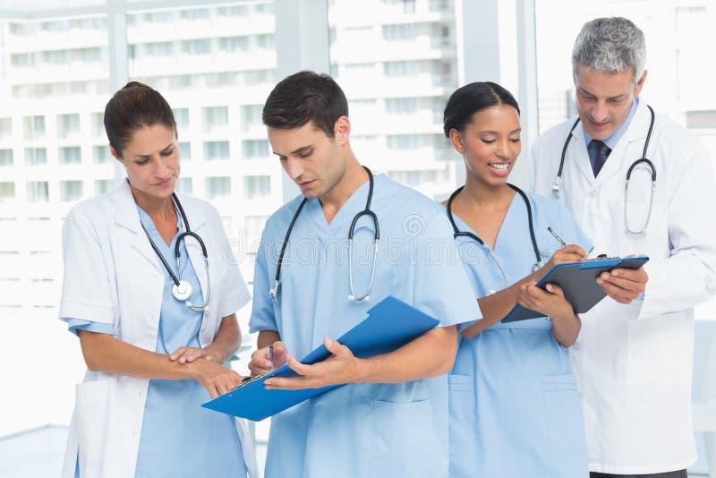 Doutores masculinos e fêmeas que trabalham em relatórios fotos de stock
