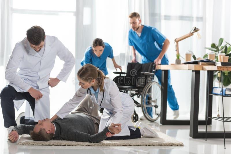 doutores novos que verificam o pulso do homem inconsciente imagens de stock royalty free