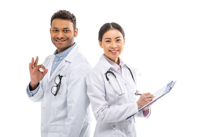 Doutores profissionais novos que estão junto e que gesticulam fotografia de stock royalty free