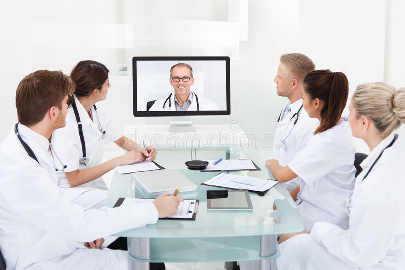 Doutores que atendem à videoconferência fotografia de stock