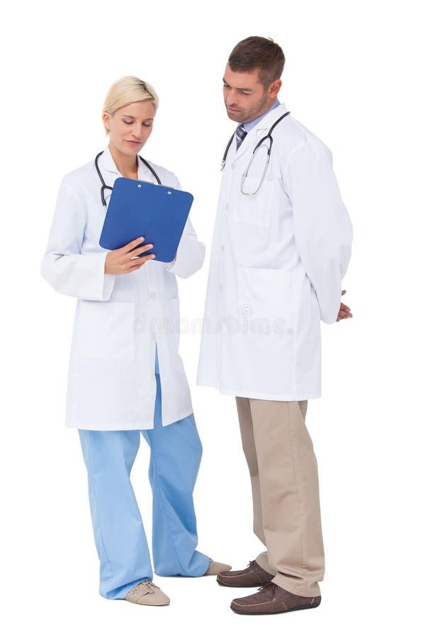 Doutores que discutem algo na prancheta imagens de stock royalty free