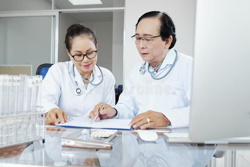 Doutores que discutem a hist?ria m?dica foto de stock