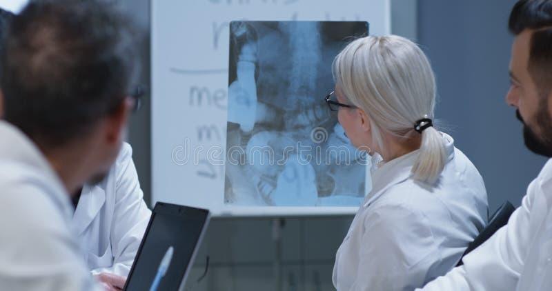 Doutores que discutem o diagn?stico de ferimento do osso foto de stock