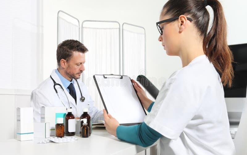 Doutores que escrevem a prescrição na mesa no escritório médico com droga fotografia de stock royalty free