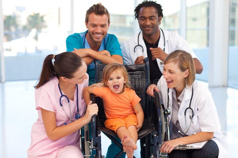 Doutores que jogam com um bebê em uma cadeira de rodas fotografia de stock