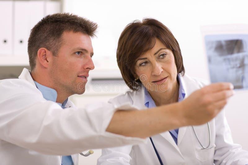 Doutores que olham a imagem do raio X foto de stock royalty free