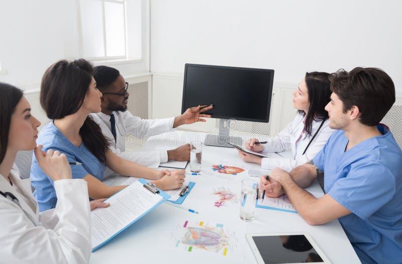 Doutores que têm a leitura e que tomam notas na sala de reunião imagens de stock royalty free