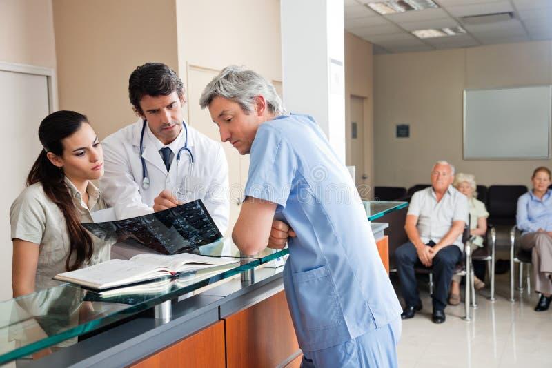 Doutores Reviewing Raio X Recepção foto de stock