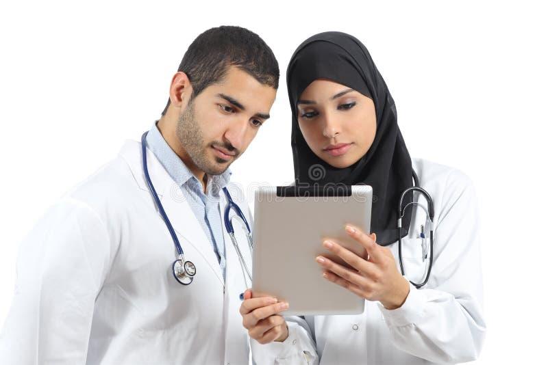 Doutores sauditas que trabalham com uma tabuleta imagens de stock royalty free