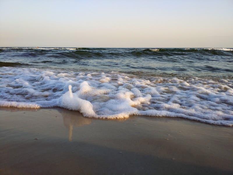 Doux et doucement vague de mer sur la plage sablonneuse Fond de coucher du soleil photo stock