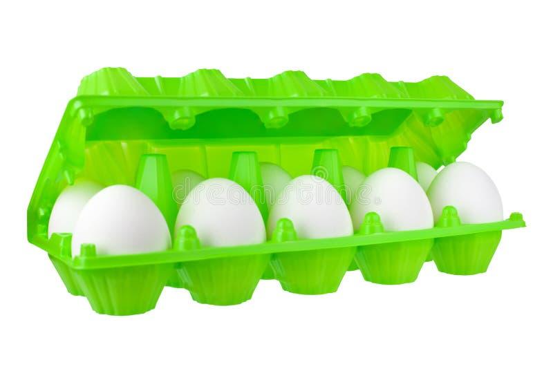 Douzaine oeufs blancs en paquet en plastique vert ouvert sur la fin d'isolement par fond blanc vers le haut de la vue de côté photographie stock