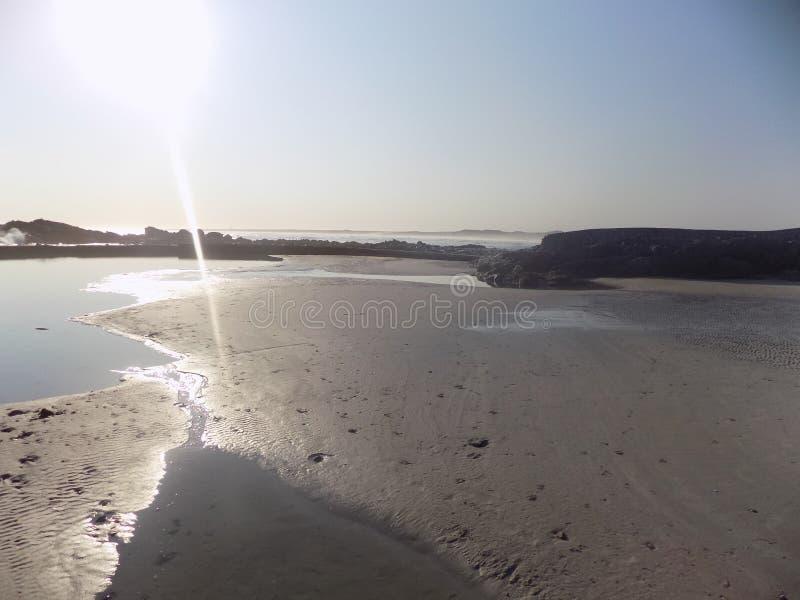 Dove la luce incontra la sabbia della spiaggia fotografia stock libera da diritti