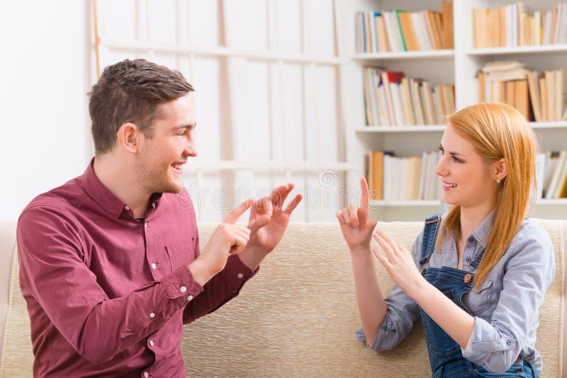 Dove mens met zijn meisje die gebarentaal gebruiken stock foto