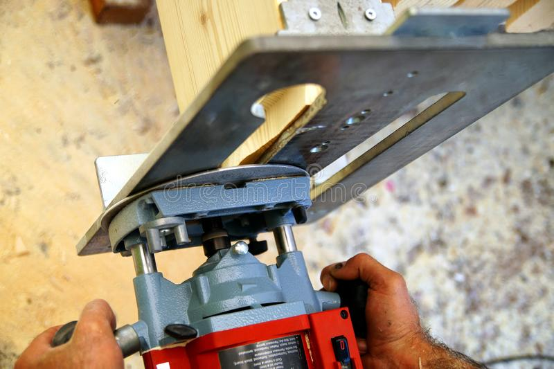 Dovetail joint. a man`s hands is working with a milling machine, while he is working outside.  milling Woodworking royalty free stock photo