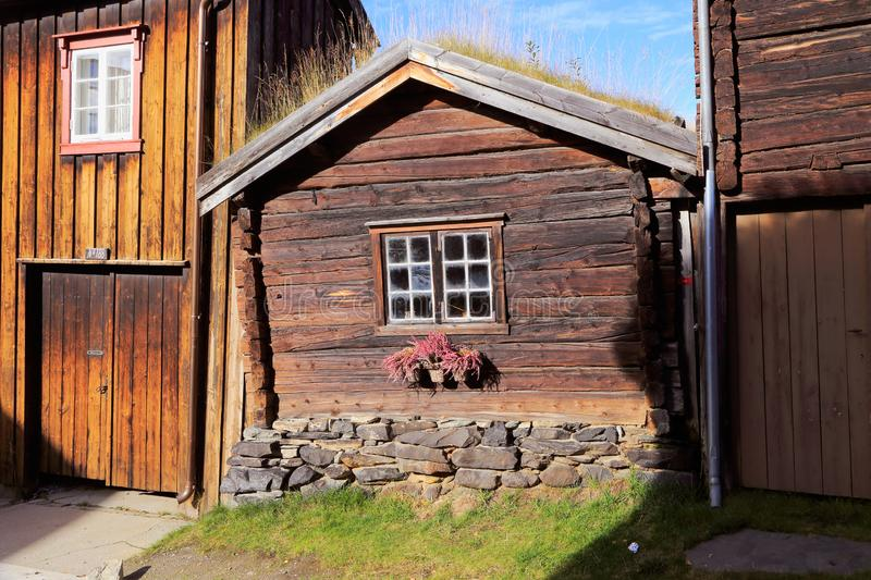 Dovetailed building. Dovetailed brown old small wooden house with grass covered roof in the Norwegian mining town of Roros royalty free stock photo
