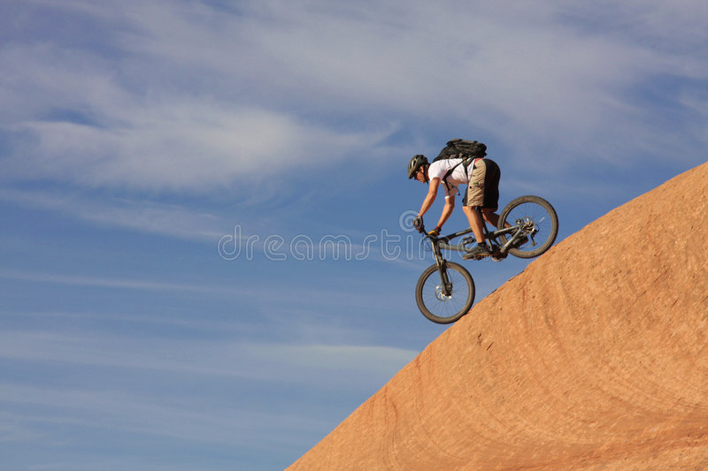 Down. A fearless mountain biker drops down a steep section of Moab's slickrock trail