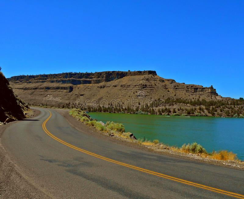 Down in the Cove. Driving through The Cove Palisades State Park - Lake Billy Chinook - Crooked River arm - near Culver, OR - Steamboat Rock to the right royalty free stock photography