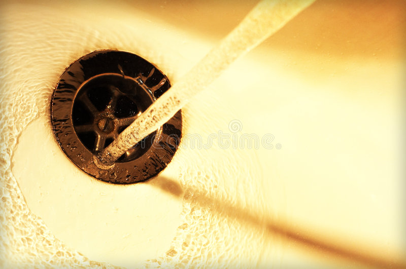 Down the drain. Tap water running in sink royalty free stock photo