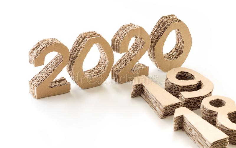 2020 with 19 and 18 down, handmade 3D numbers made of reused cardboard paper, on white background. New year concept. 2020 with 19 and 18 down, handmade 3D stock photo